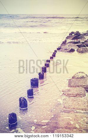 Retro Old Film Stylized Photo Of A Breakwater On Beach
