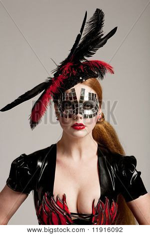 Long haired woman in haute couture clothes and mask