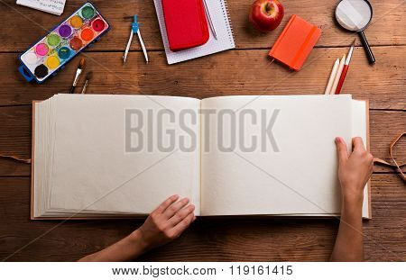 Hands of man with empty notebook. Various school supplies.