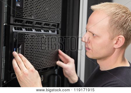 Close-up of It consultant installing server in datacenter