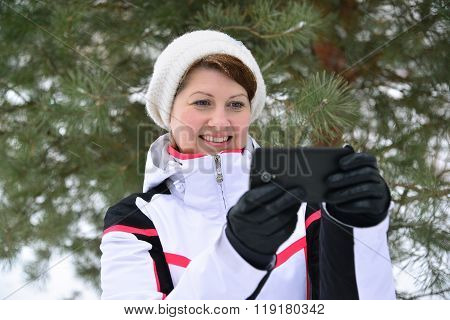 Sport Woman With A Smartphone In  Pine Winter Forest