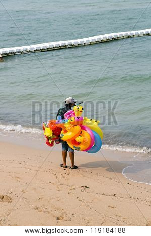 Thai man sells inflatable toys at the beach