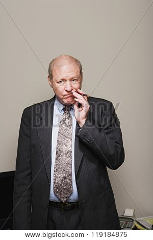 Mature businessman chewing his pen