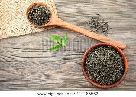 Dry tea with green leaves in wooden spoon and bowl on table background