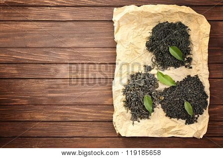 Dry tea with green leaves on wooden table background, copy space