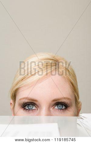 Woman peeking over filing cabinet