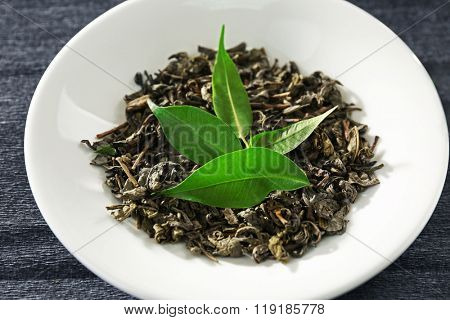 Granulated tea with green leaves in white saucer closeup
