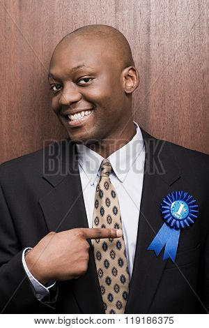 Businessman pointing at his rosette