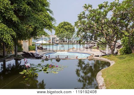 THAILAND, PATTAYA, MARCH, 26, 2015 - Modern swimming-pool with clear turquoise water in a beautiful tropical garden, Pattaya, Thailand