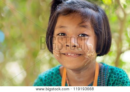 SANGHLABURI, THAILAND, JANUARY 24, 2016 : A Thai little girl selling souvenir stuffs is posing near a temple in Sanghlaburi, Thailand