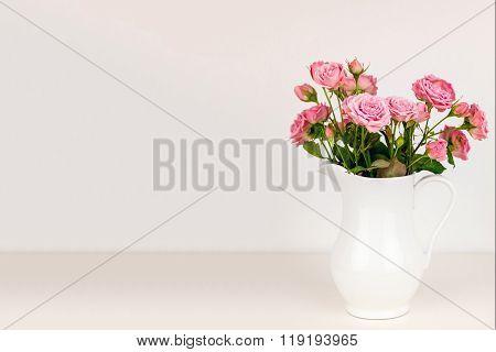 Pink flowers in white jug. Roses in vase.