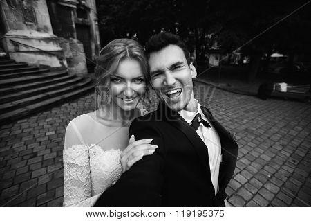 Handsome Groom And Blonde Bride Taking Selfie In European Street B&w