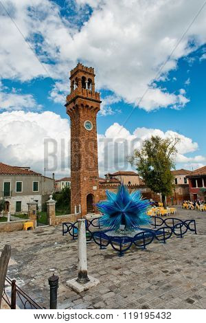 VENICE, ITALY - 17 OCTOBER 2015: Glass artwork of blue star and clock tower on Murano island in Venice, Italy
