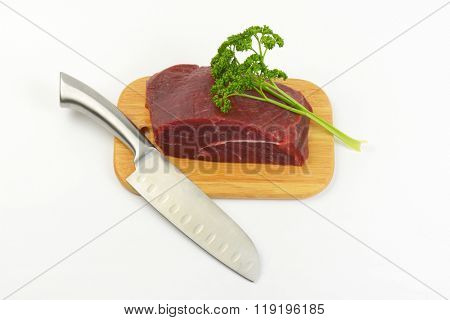 chunk of raw beef meat, parsley and sharp knife on wooden cutting board
