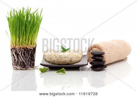 Toalla Spa, jabón y pasto de trigo sobre fondo blanco