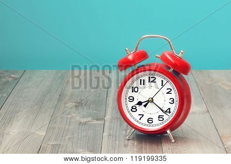 Red Retro Alarm Clock On A Wooden Table.