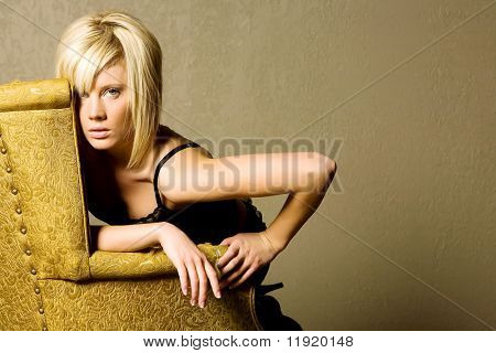 Beautiful young blond girl on a chair