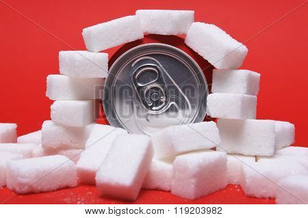 Cola Refreshing Drink Can And Lot Of White Sugar Cubes Representing The Big Amount Of Calories