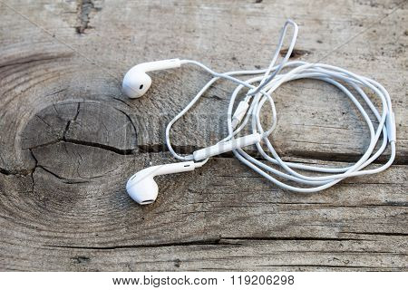 White Earphone On A Old Wood Surface