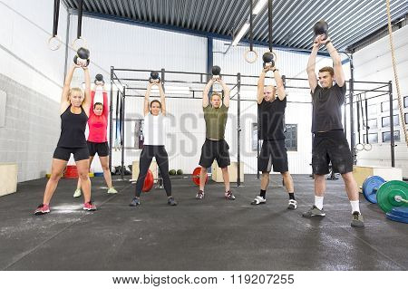 Team workout with kettlebells at fitness gym