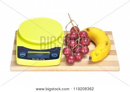 Crimson Grape, Banana And Electronic Kitchen Scale On Bamboo Chopping Board