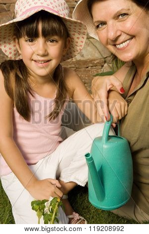 Girl and grandmother with watering can