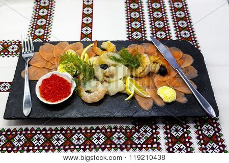 Banquet menu. Fish assortment on a beautiful black platter with red fish, shrimp, caviar, smoked salmon,turbot. A great appetizer