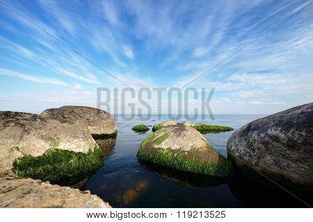 Granite rocks on the Baltic sea shore in calm water. Beautiful cloudscape.