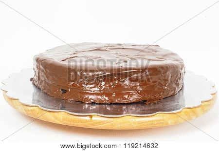 Sacher Chocolate Cake On A Silver Plate On Wooden Board Towards White