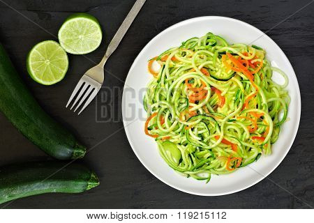 Healthy zucchini noodle dish with carrots and lime
