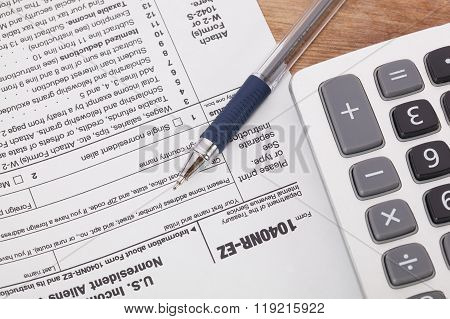 Calculator And Pen On Tax Form Background