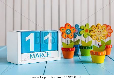 March 11th. Image of march 11 wooden color calendar with flower on white background.  Spring day, em