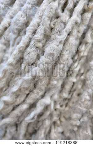 Beige abstract background with curly fluffy woolen ropes