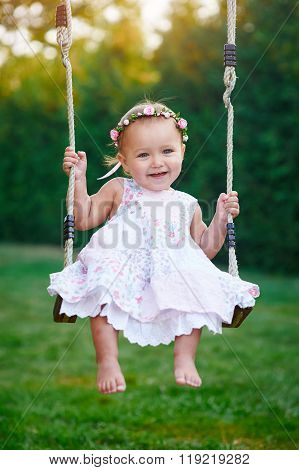 Adorable baby girl wearing white dress enjoying swing