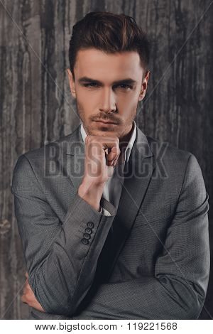 Attractive Sexy Man In Business Suit On The Grey Background Touching Chin