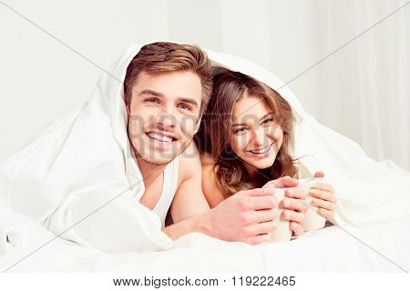 Cute Couple In Love  Basking Under Blanket With Coffee In The Morning