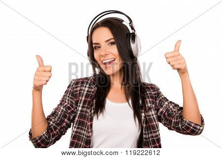 Cheerful Happy Girl Listening Music In Headphones And Thumbs Up