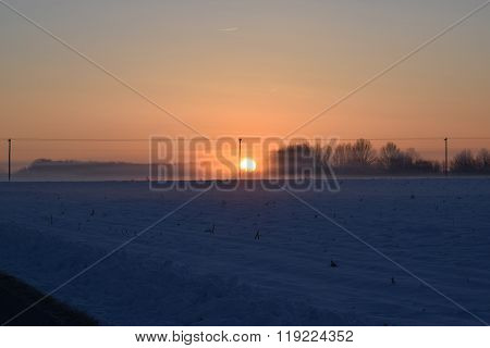 a bitterly cold winter sunrise with a haze