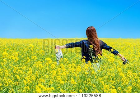 Young Woman Standing In Yellow Rapeseed Field.