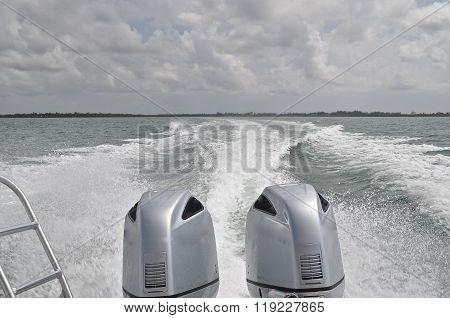 Huge twin boat motors leave a wake