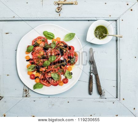 Ripe village heirloom tomato salad with olive oil and basil over light blue wooden background