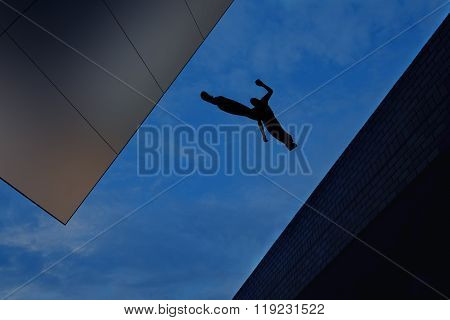 Man Jumping Over Building Roof Against Blue Sky Background
