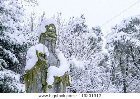 Falling Snow At Guanyin Statue In A Winter With Snow Covered Trees.