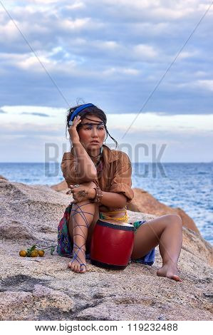 Woman shaman with drum, in mountain sea. Ethnic fashion photoshoot.