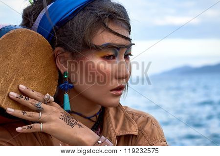 Woman shaman with drum, near sea. Ethnic fashion photoshoot.