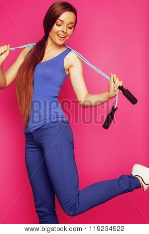 young happy slim girl with skipping rope on pink background smiling sweety cute