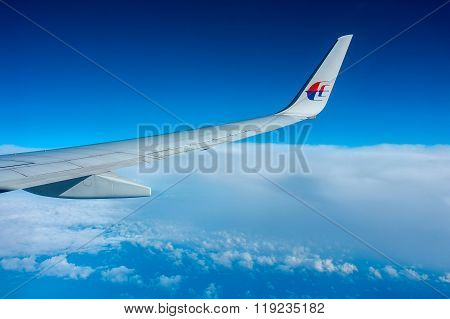 Aerial view of the cloudy,blue sky and airplane wing as seen through window of an aircraft.