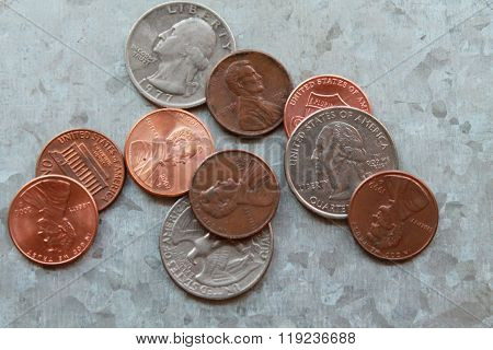 Quarters and pennies on a silver metal background