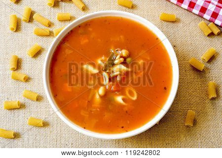 high-angle shot of a bowl with minestrone, a typical italian soup, with vegetables and pasta, on a table set with a rustic tablecloth