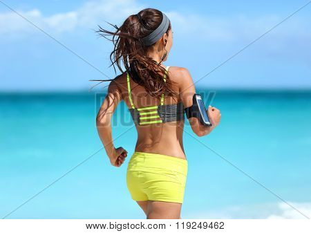 Running motivation - runner training with music seen from behind jogging in fashion yellow straps sports bra and neon shorts outfit wearing wireless earphones on summer beach background.